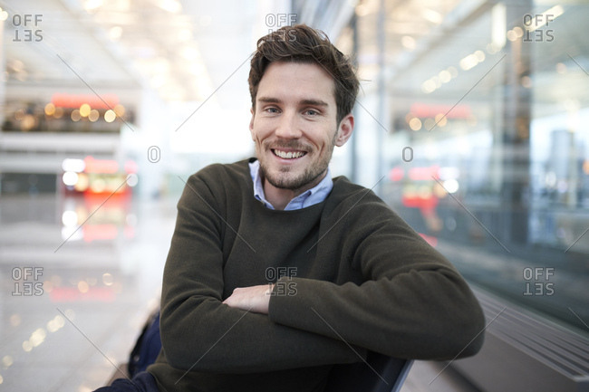 Portrait of smiling young businessman sitting in waiting area
