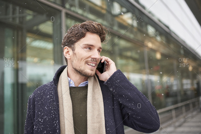 Smiling young businessman on cell phone in snow