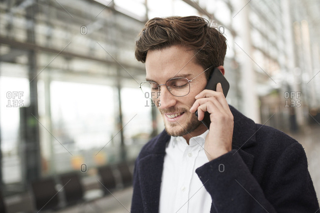 Smiling young businessman wearing glasses talking on cell phone