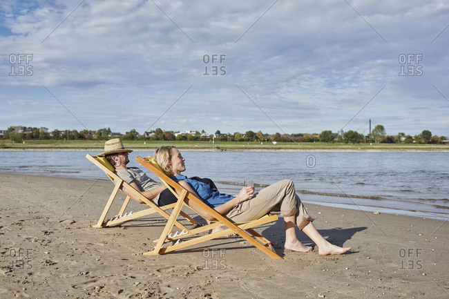 Young couple in deckchairs relaxing at the riverbank