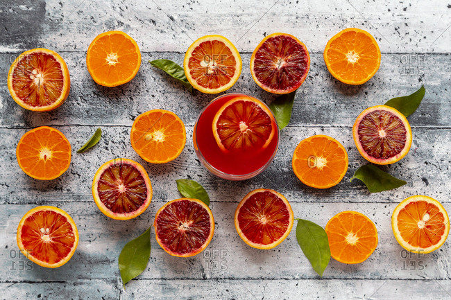 Halves of blood oranges- tangerines and glass of blood orange juice