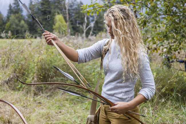 Archeress sorting bow and arrows in nature