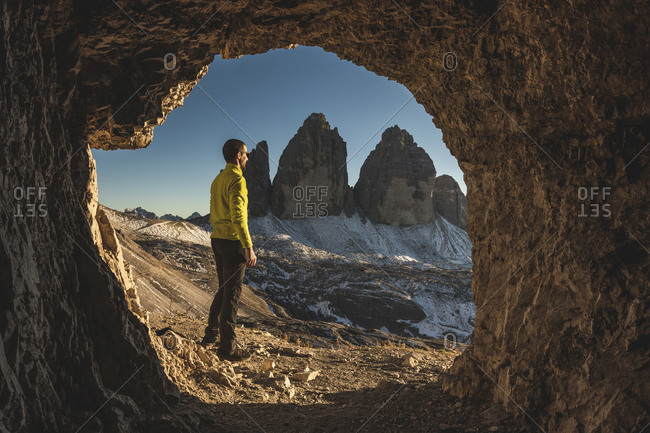 Italy- Tre Cime di Lavaredo- man hiking and standing in front of a cave with the three peaks in background