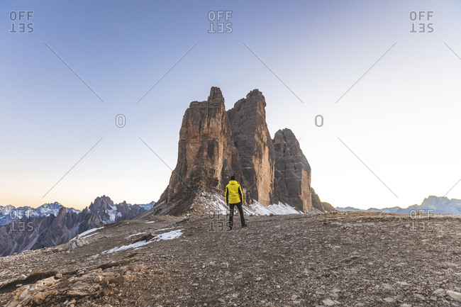 Italy- Tre Cime di Lavaredo- man hiking and standing in front of the majestic three peaks