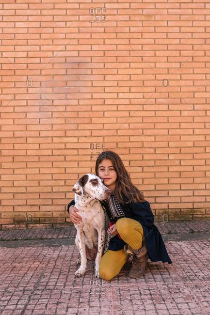 Beautiful girl is hugging her dog in the street with a nice brick background