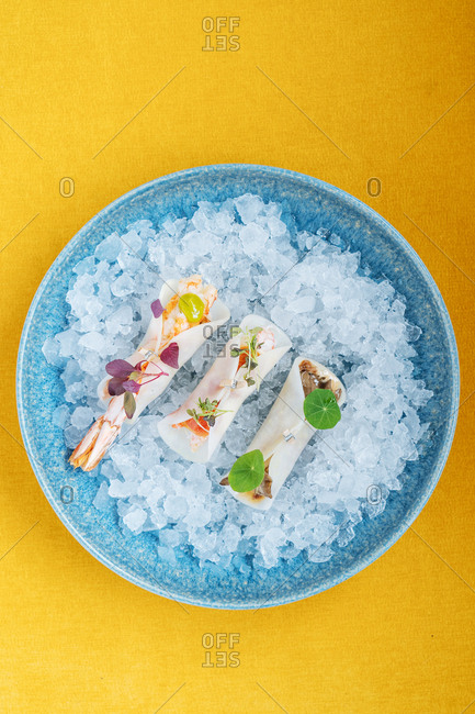 Sushi on ice on a yellow background