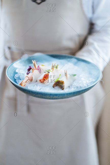 Chef holding sushi on blue plate with ice