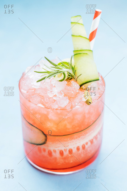 Close up of an icy cocktail with cucumber and rosemary garnish