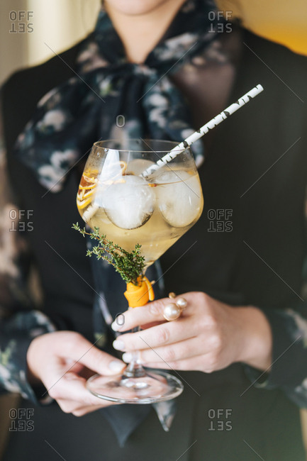 Woman holding cocktail in large stemware