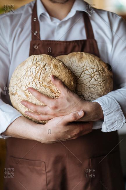 Baker holding fresh baked loaves of bread