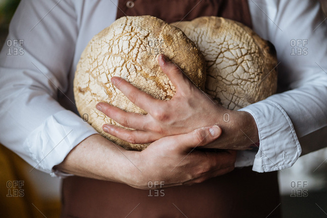 Baker holding a few fresh baked loaves of bread