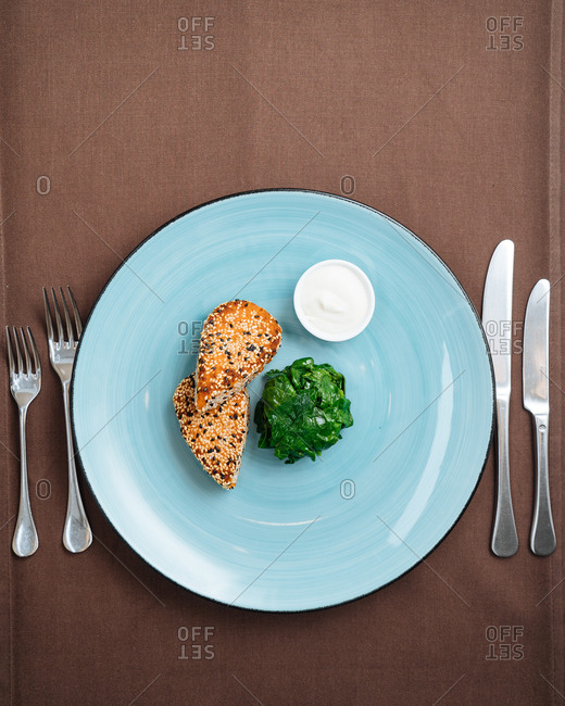 Sesame crusted fish and spinach served on a table