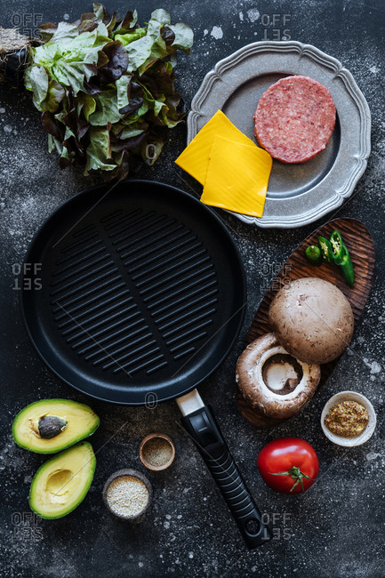 Frying pan surrounded by raw ingredients for cheeseburgers