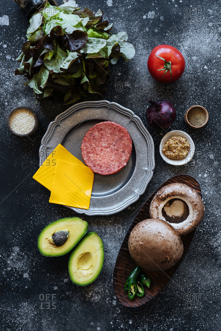 Raw hamburger with cheese and vegetables on dark surface