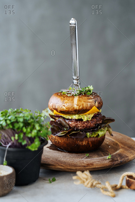 Juicy cheeseburger with knife through it and micro greens