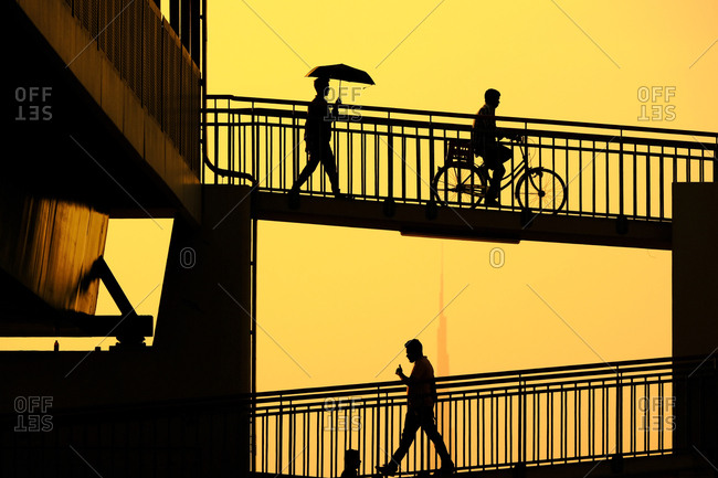 Dubai, United Arab Emirates - November 1, 2018: Silhouette of men on bridge in front of the Burj Khalifa