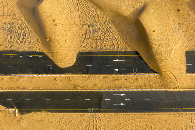 Wind blown sand partially covering highways in the desert