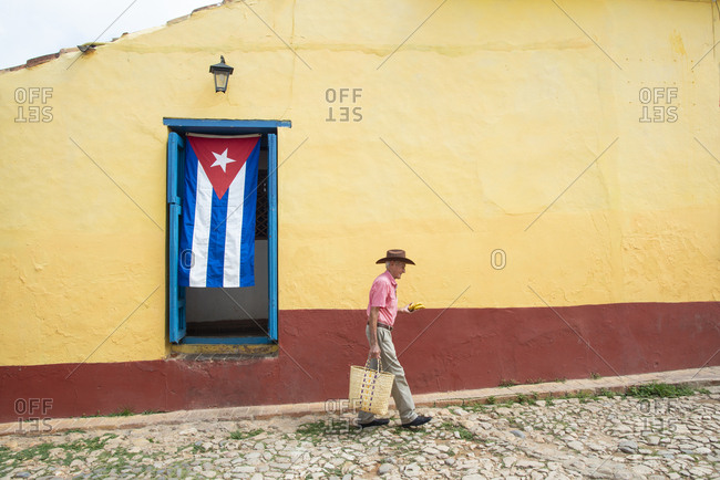 Man walking down to the plaza to sell some bananas in Trinidad, Cuba