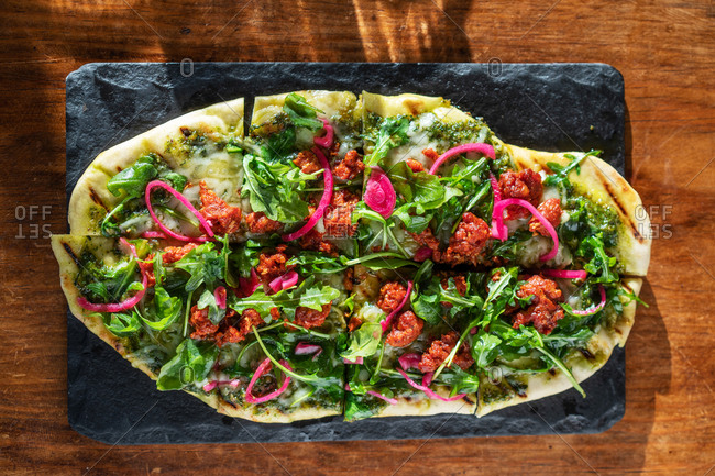 Overhead view of a flatbread pizza on slate