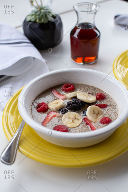 Quinoa breakfast bowl with fruit on a white table