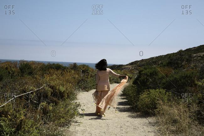 Woman walking on sandy path by the ocean