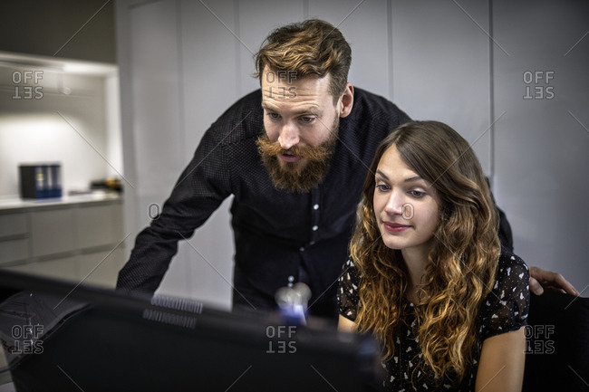Businessman and businesswoman looking at computer in office