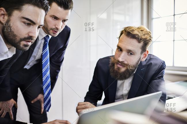 Focused businessmen looking at laptop in office