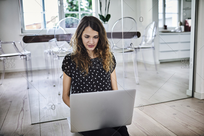 Young businesswoman sitting on the floor in office using laptop