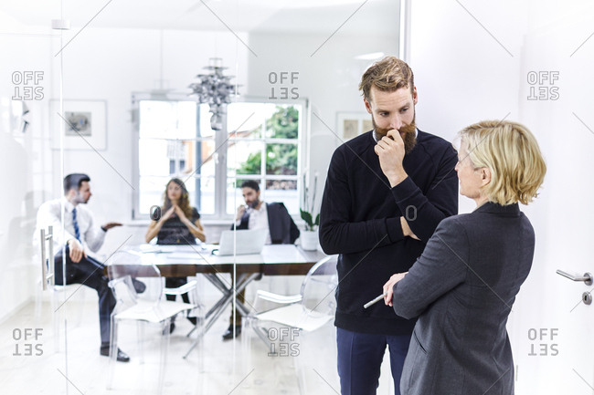 Businessman and businesswoman talking in office with colleagues in background