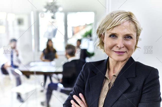 Portrait of a confident mature businesswoman in office with colleagues in background
