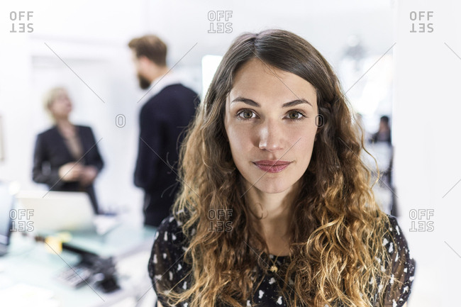 Portrait of a young businesswoman in office with colleagues in background
