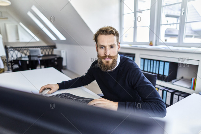Bearded businessman using computer at desk in office