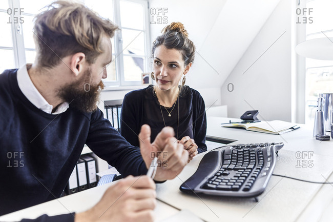 Businessman and businesswoman at desk in office