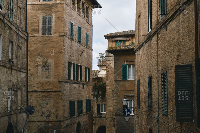 March 17, 2019: Exterior of old masonry facades of buildings on narrow city street of Toscana, Italy