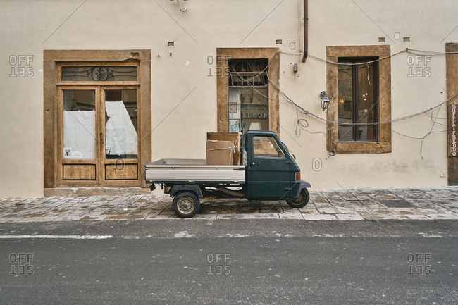 March 18, 2019: Side view of small van with three wheels parked on sidewalk of street with old building facade, Toscana