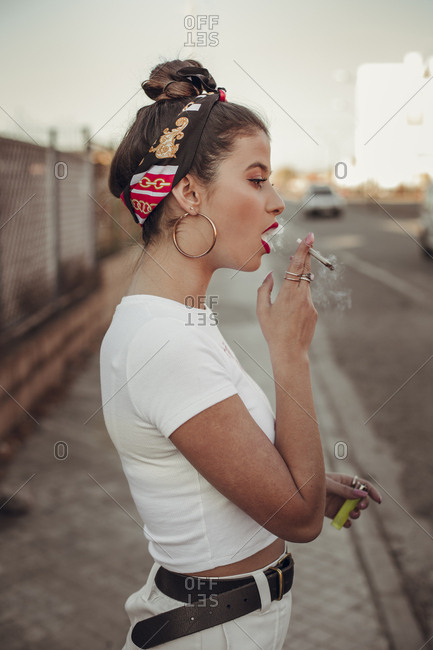 Urban Portrait of a beautiful brunette girl with a hair band smoking a rolling cigarette