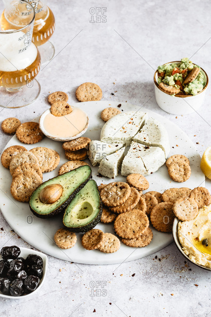 Vegan party platter with crackers, cheese and avocado