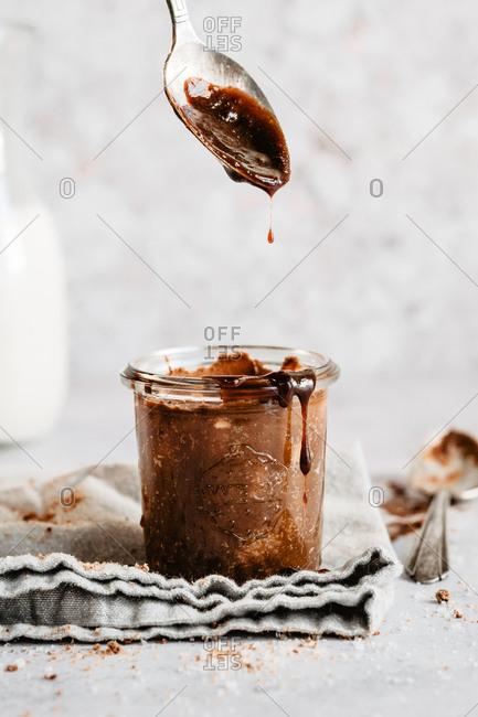 Drizzling vegan caramel  into a jar