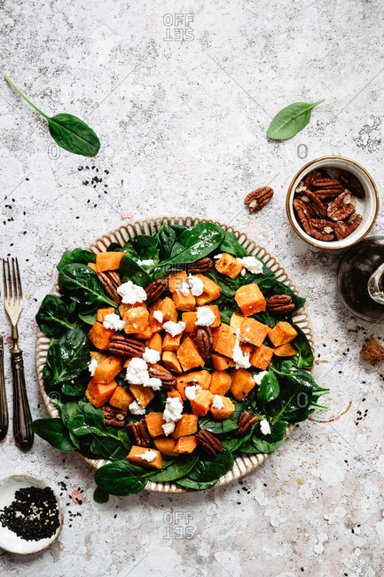 Vegetarian spinach sweet potatoes  salad with pecans and goat cheese onto a grey surface
