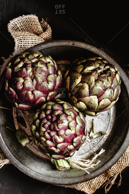 Green and purple  raw artichokes on pan