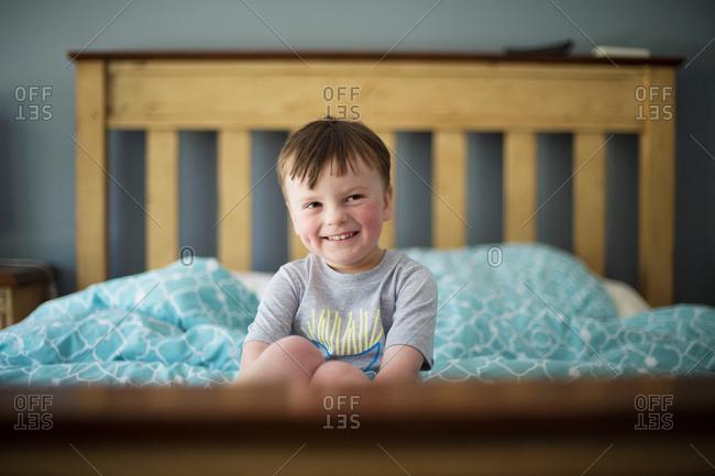 Cheeky boy sitting on bed