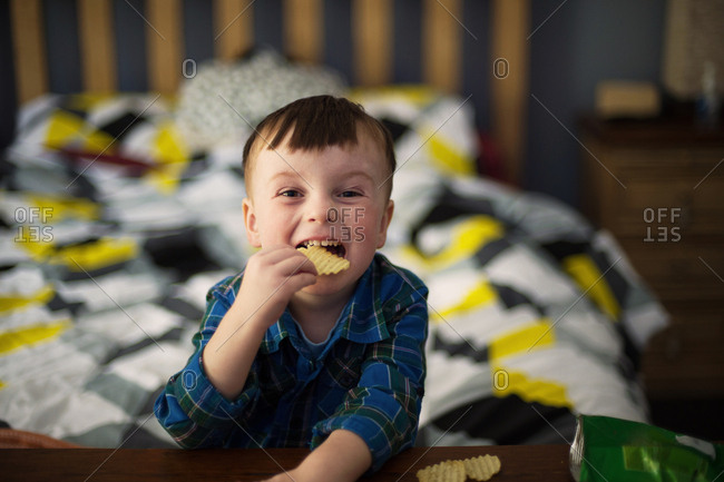 Boy eats a bag of chips in bed