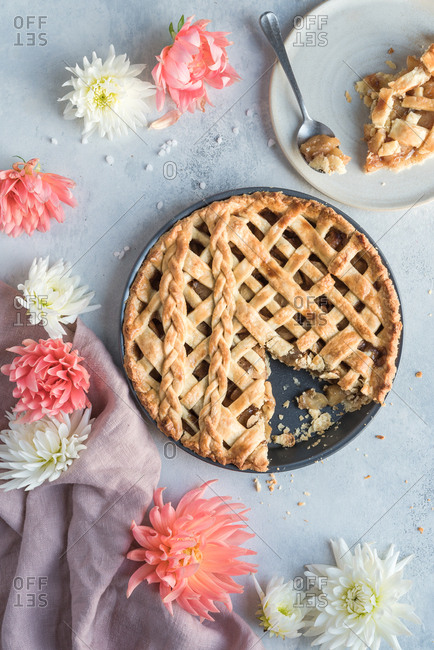 Pie in pie-tin with one slice taken out sitting on a plate with a spoon. Accompanied by flowers and a napkin.