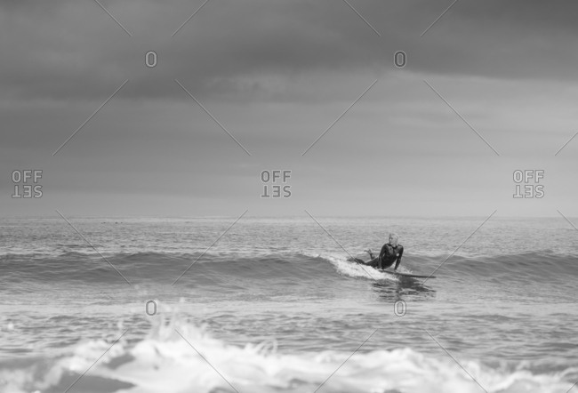 Platinum blonde girl in a wetsuit paddling on her surfboard