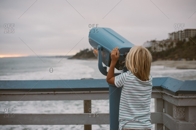 Boy on pier over looking the ocean with coin operated viewfinder