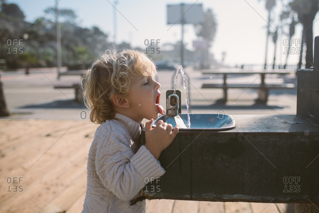Child at beach park drinking from water fountain
