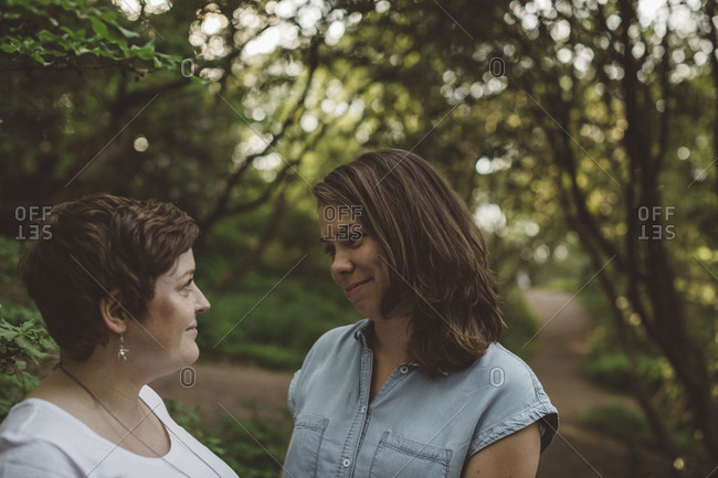 Lesbian couple smiling in forest