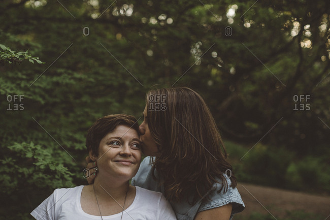 Lesbian couple kissing in forest