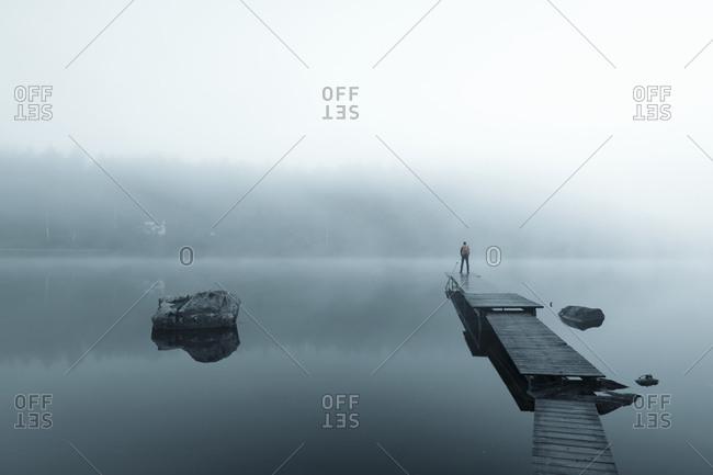 Man on pier in lake in morning fog