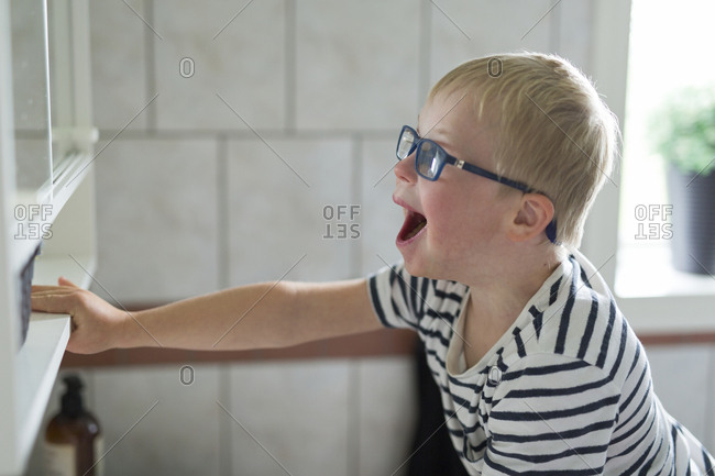 Boy yawning in bathroom